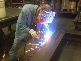 man welding a large metal beam
